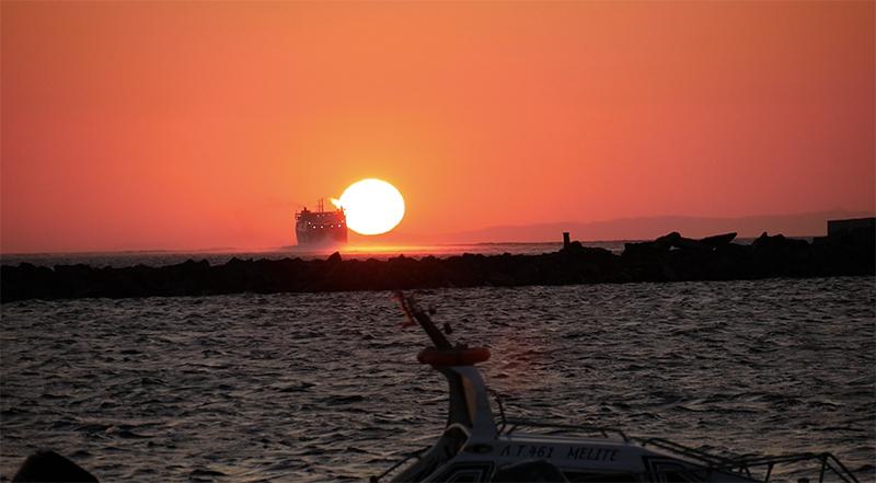 Prachtige zonsondergang bij de haven van Tinos