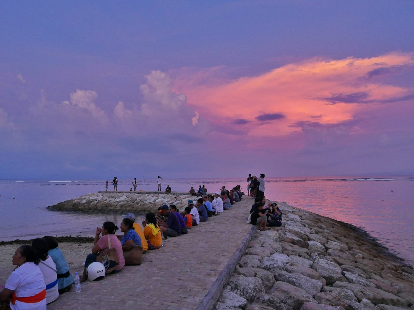 Balinezen zitten op de pier te kijken naar het podium