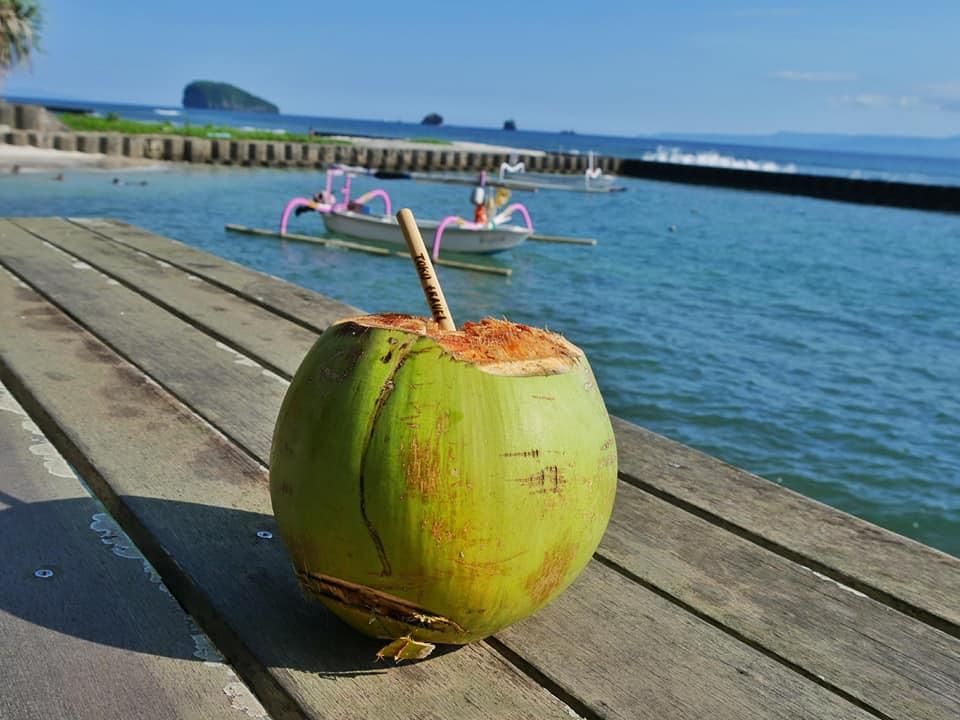 Drinken uit een kokosnoot op een paradijselijk plekje