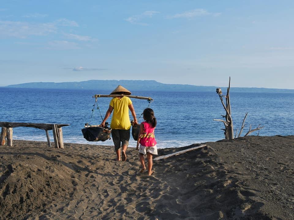 Balinese vrouw haalt het zoute water op, voordat ze het uitstrooit