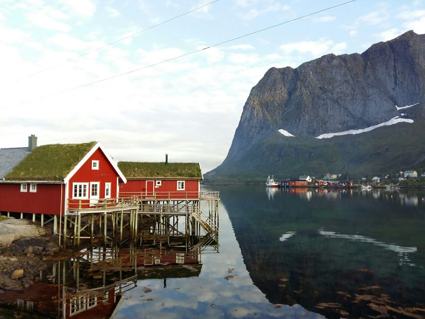 Rode vissershuisjes tegenover hoge bergen