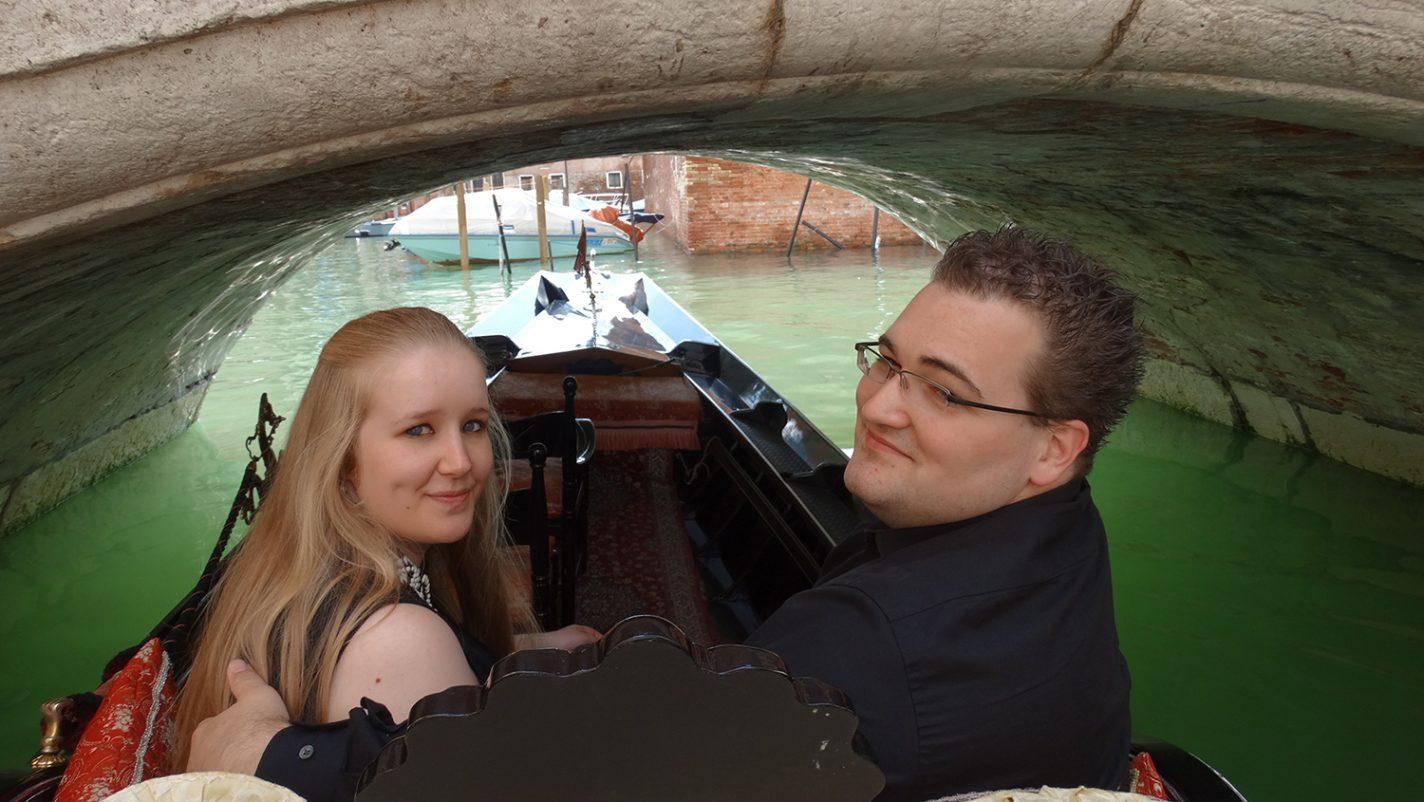 In een gondel onder lage bruggetjes door in Venetië