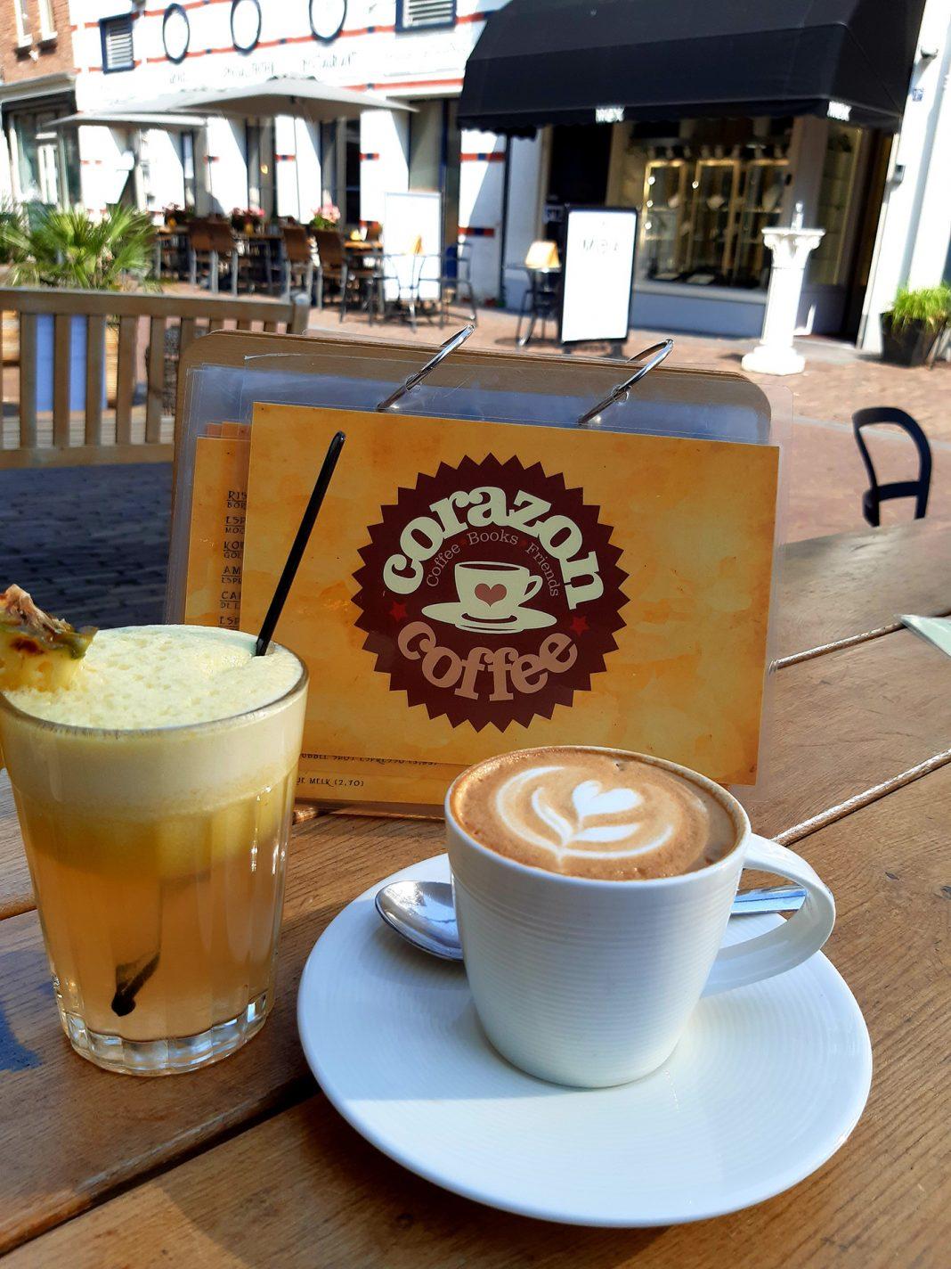 Cappuccino met een kunstwerkje en vers ananassapje bij Coffee Corazon