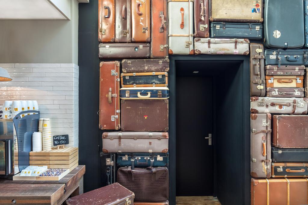 Een muur van vintage koffers bij de receptie van Hotel van Heeckeren