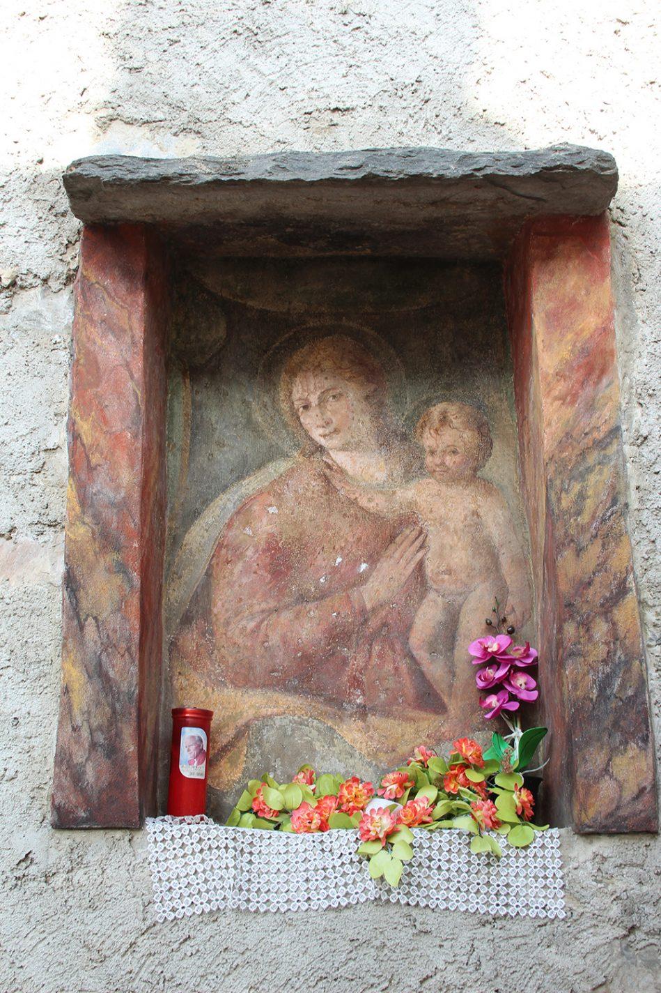 Fresco/mini altaar in een muur langs de kant van de weg