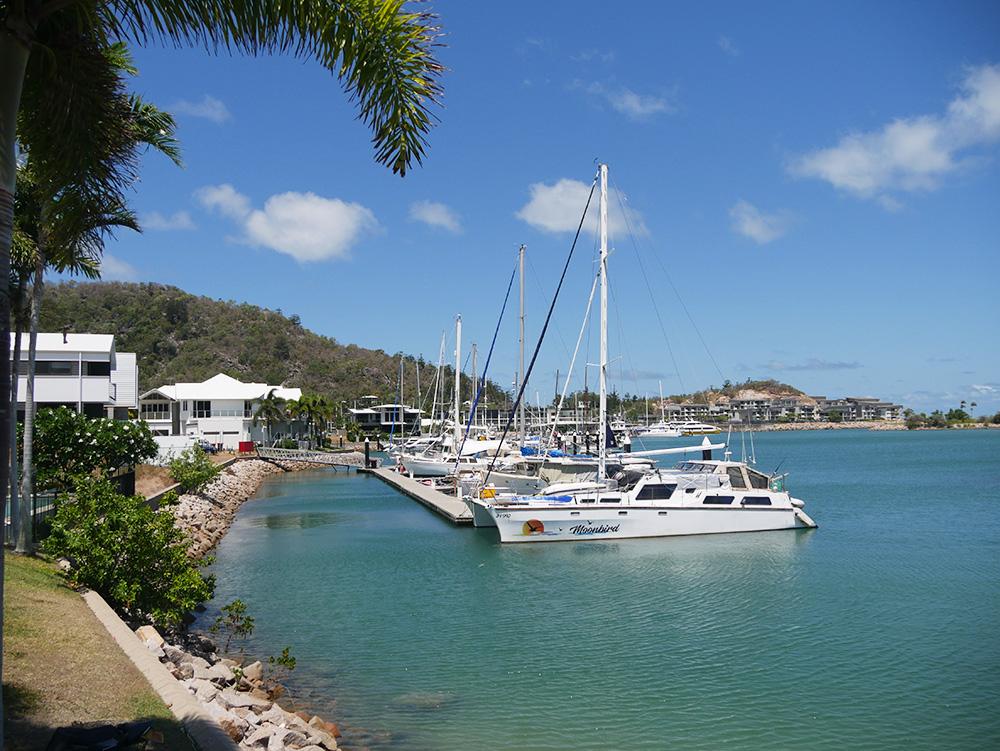 Bootjes bewegen op het water in de haven van Nelly Bay
