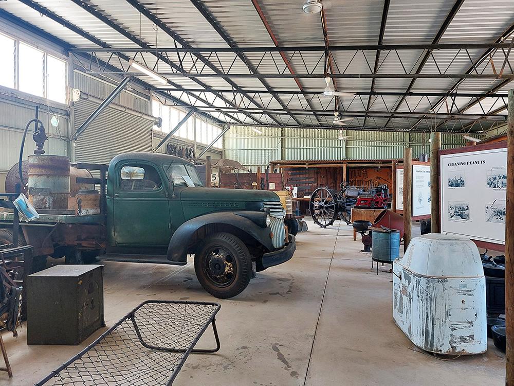 Zaal vol met oude wagens, landbouwmachines en materieel